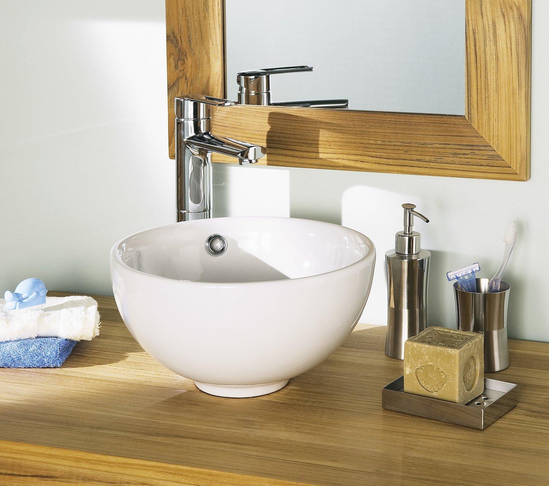 Un meuble de salle de bains en bois avec une vasque blanche posée