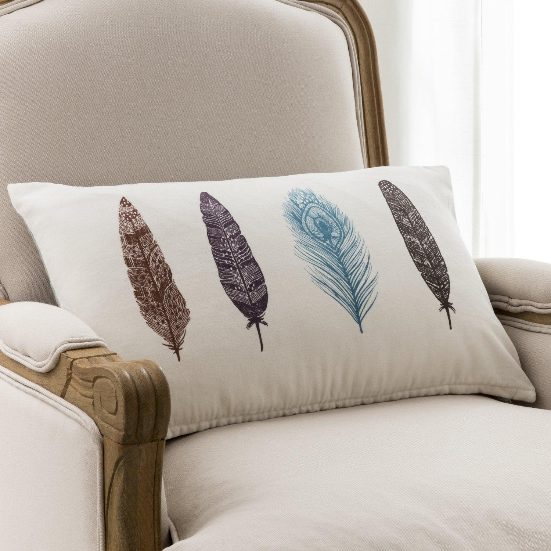 un coussin blanc aux motifs plumes pour un salon au style romantique