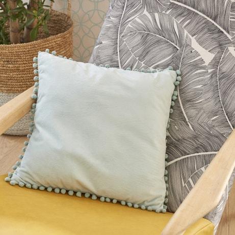 Un coussin gris bleu bordé de pompons pour apaiser une ambiance colorée
