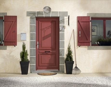 Une façade de maison classique avec porte d'entrée et volets battants couleur brique