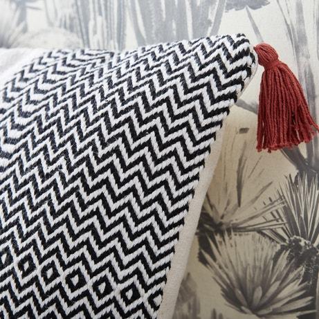 Un coussin géométrique avec des pompoms rouges