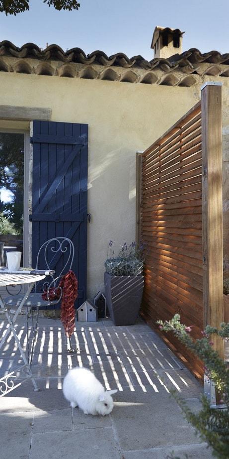 Un panneau bois persienné robuste qui laisse entrevoir la lumière