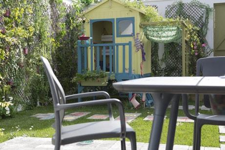 Un jardin bien aménagé avec une maisonnette sur pilotis et un salon de jardin