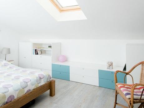 Rangement blanc et bleu sous-pente dans la chambre d'Emilie à Camblanes