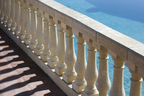 Une terrasse avec balustres et vue sur la piscine