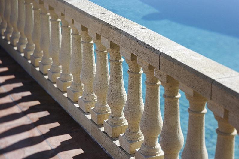 Une terrasse avec balustres et vue sur la piscine leroy for Lustre terrasse exterieur