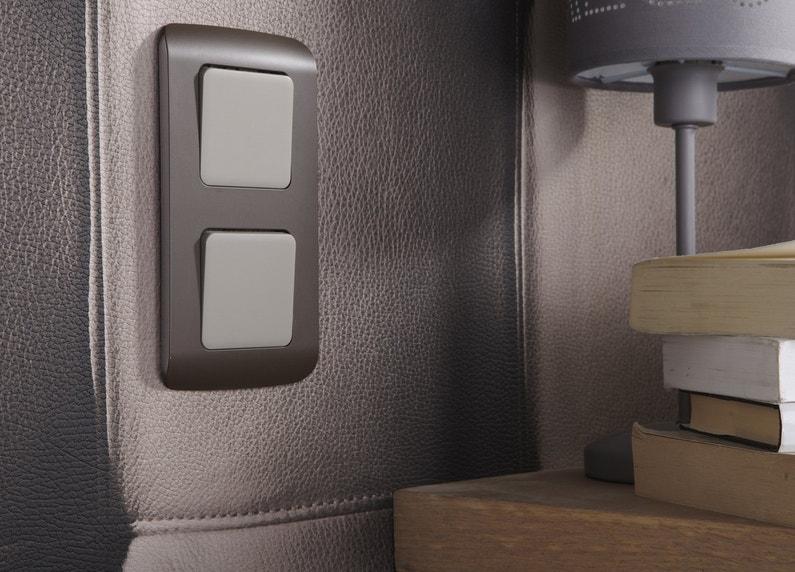Un double interrupteur poussoir vertical brun et blanc
