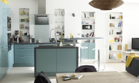 Une cuisine bleue ouverte sur le salon