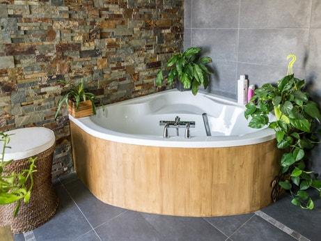 Une baignoire d'angle avec tablier en bois pour un coin zen dans la salle de bains de Christel à Inzinzac Lochrist