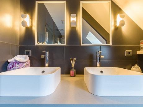 Coin coiffeuse avec deux vasques et deux miroirs éclairés dans la salle de bains de Cécile à Veretz