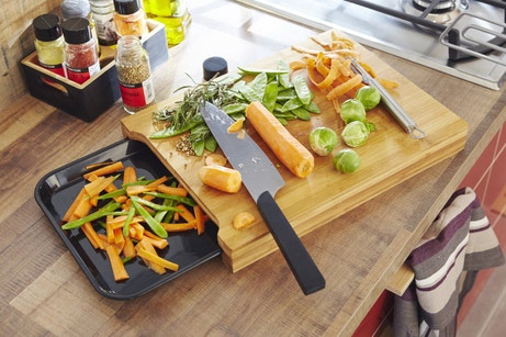 Planche à découper en bambou recueillant les épluchures de légumes
