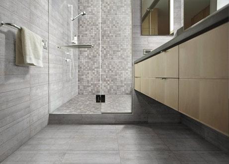Salle de bains grise avec douche et porte vitrée