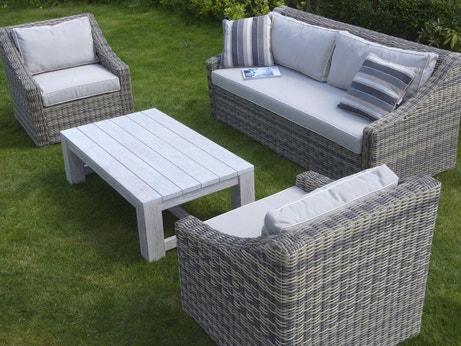 Un salon de jardin avec une table en bois blanchi