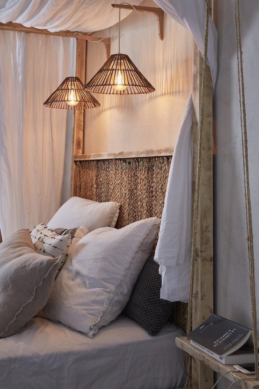 Une tête de lit avec des suspensions qui servent de lampe de